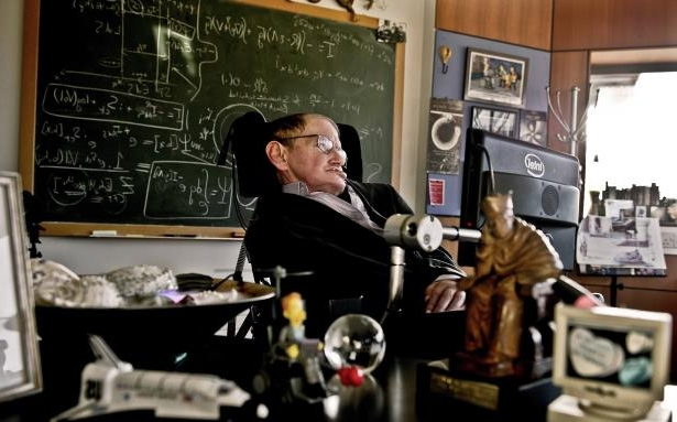 a person standing in front of a store: Dr. Hawking in his office at the University of Cambridge in December 2011. His only complaint about his speech synthesizer, which was manufactured in California, was that it gave him an American accent.