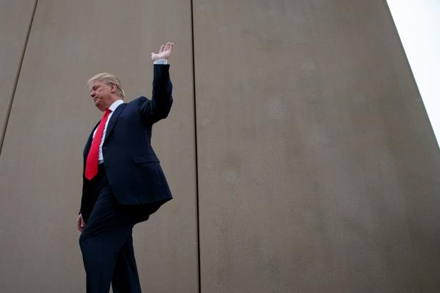 a person standing posing for the camera: President Trump talks with reporters as he gets a briefing on border wall prototypes on Tuesday, March 13, 2018, in San Diego.
