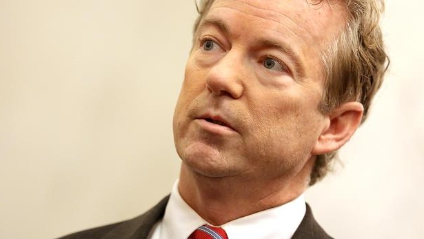 Rand Paul wearing a suit and tie smiling at the camera