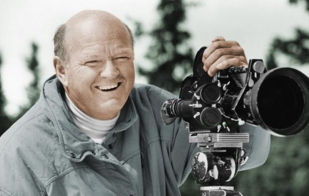 Slide 32 of 59: In this undated photo provided by the Warren Miller Co., Warren Miller is shown posing for a photo with a film camera.