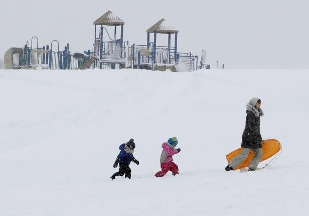 Slide 37 of 109: Christina Mesavage leads family friend, Una Mayer, center, and her son, Jude, up a sledding hill at the Eastern Promenade while enjoying the snow during a nor'easter on March 8, 2018, in Portland, Maine.