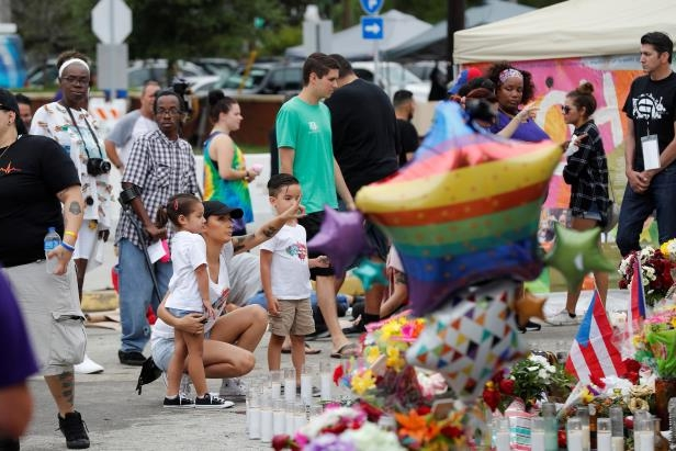 Slide 4 of 20: Guests visit the memorial outside the Pulse Nightclub on the one-year anniversary of the shooting in Orlando, Florida, U.S., June 12, 2017.