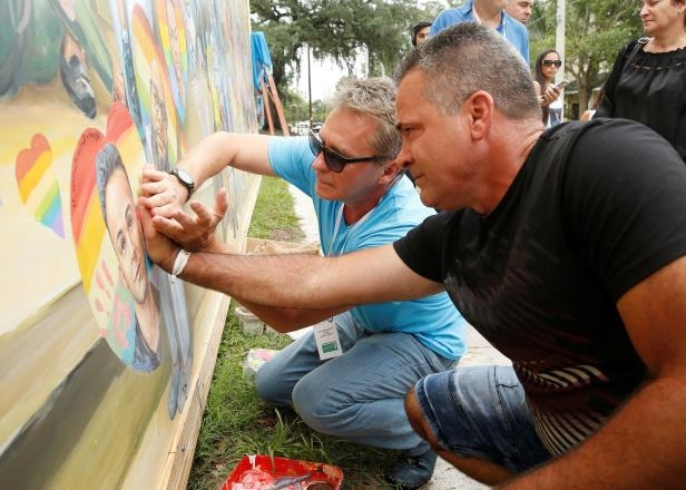 Slide 9 of 20: Saul Barrios (L) leaves his handprint on a mural that contains an image of his deceased son Alejandro Barrios Martinez, with the help of artist Yuri Karabash, at the memorial outside the Pulse Nightclub on the one-year anniversary of the shooting in Orlando, Florida, U.S., June 12, 2017.