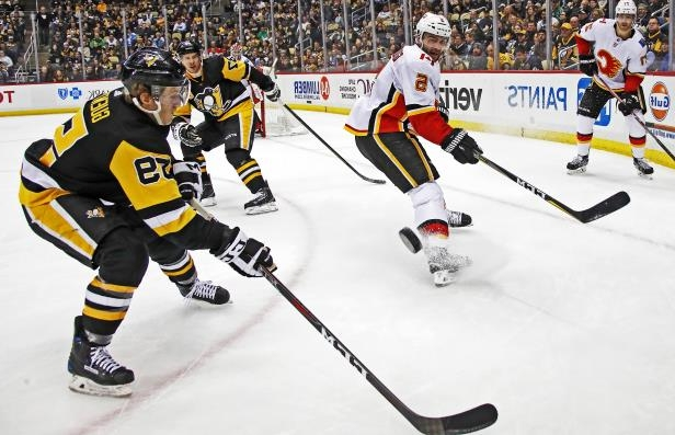 Slide 65 of 75: Calgary Flames' Mark Giordano (5) clears the puck between Pittsburgh Penguins' Sidney Crosby (87) and Jake Guentzel (59) during a power play in the second period of an NHL hockey game in Pittsburgh, Monday, March 5, 2018.