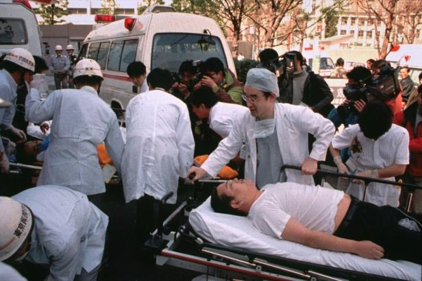 FILE - In this March 20, 1995 file photo, subway passengers affected by sarin nerve gas in the central Tokyo subway trains are carried into St. Luke's International Hospital in Tokyo. Tuesday, March 20, 2018 marks 23 years since members of the Aum Shinrikyo cult punctured plastic bags to release sarin nerve gas inside subway cars, sickening thousands and killing 13. Cult leader Shoko Asahara and a dozen followers have been sentenced to death for that and other crimes that killed 27 in all. (AP Photo/Chiaki Tsukumo, File)