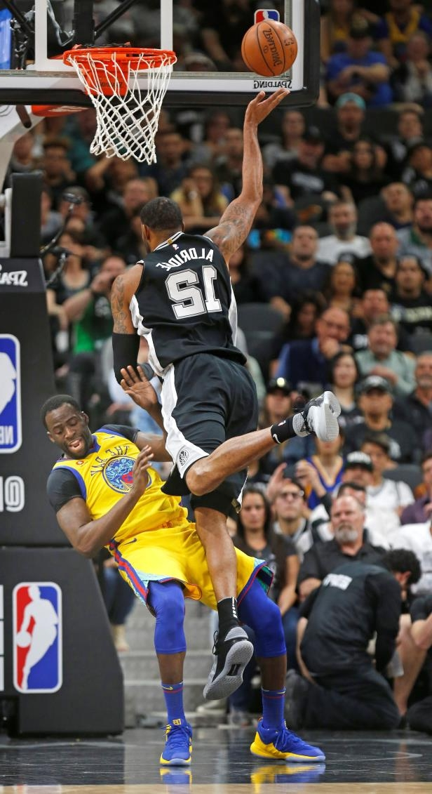 Golden State Warriors forward Draymond Green (23) takes a charge from San Antonio Spurs forward LaMarcus Aldridge (12) during the first half of an NBA basketball game, Monday, March 19, 2018, in San Antonio. (AP Photo/Ronald Cortes)