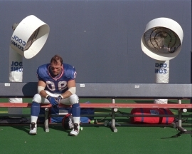 FILE - In this Sept. 14, 1997, file photo, New York Giants linebacker Corey Widmer sits on the team bench in front of two Cool Zone fans after losing to the Baltimore Ravens, 24-23, at Giants Stadium in East Rutherford, N.J. The Montana Football Hall of Fame inducted eight new members over the weekend, but Widmer declined his nomination saying concussions he suffered while playing football