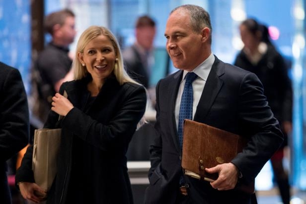 a group of people standing next to a person in a suit and tie: Scott Pruitt, the Environmental Protection Agency administrator, with his top policy adviser, Samantha Dravis, at Trump Tower in 2016. Ms. Dravis is said to be resigning.