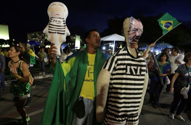 A demonstrator against Brazil's former President Luiz Inacio Lula da Silva holds dolls dressed as an inmate featuring the face of da Silva, outside the National Congress in Brasilia, Brazil, Wednesday, April 4, 2018. Brazil's top court could rule as soon as today whether da Silva can stay out of prison while appealing a corruption conviction, a decision that could radically alter October's presidential election in Latin America's largest nation. (AP Photo/Eraldo Peres)