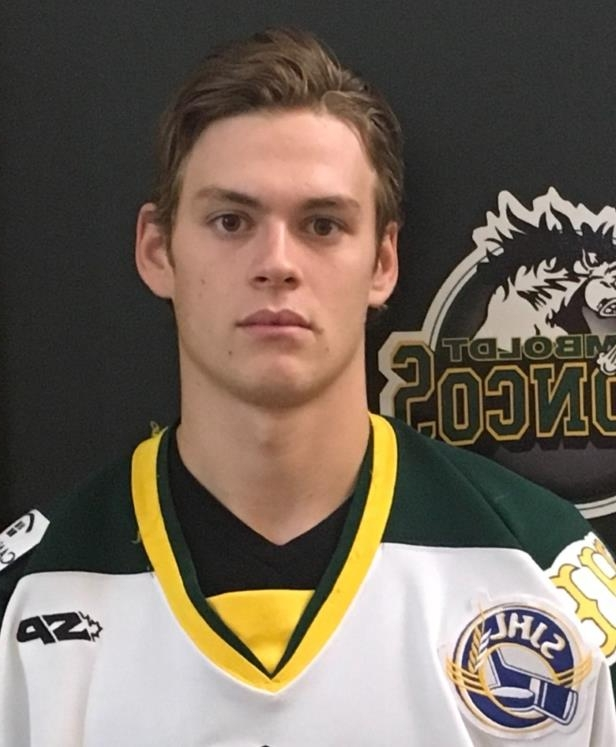 a man holding a sign: Matthieu Gomercic plays for the Humboldt Broncos and was on the bus when it crashed, but survived the crash.