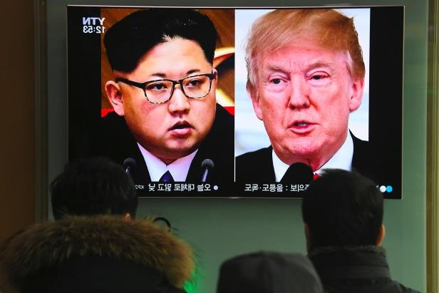 People watch a television news report showing pictures of US President Donald Trump (L) and North Korean leader Kim Jong Un at a railway station in Seoul on March 9, 2018.