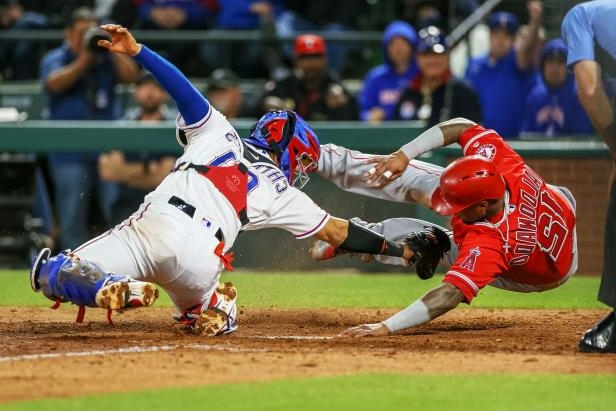 Slide 12 of 77: ARLINGTON, TX - APRIL 09: Texas Rangers Catcher Robinson Chirinos (61) attempts to tag Los Angeles Angels Catcher Martin Maldonado (12) at the plate but Maldonado (12) is called safe after a review during the game between the Los Angeles Angels and Texas Rangers on April 9, 2018 at Globe Life Park in Arlington, TX.  (Photo by Andrew Dieb/Icon Sportswire via Getty Images)