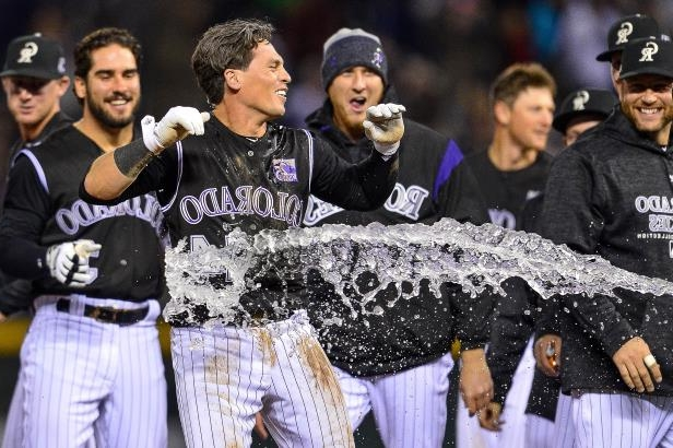 Slide 31 of 77: DENVER, CO - APRIL 7: Tony Wolters #14 of the Colorado Rockies celebrates and is doused with water after earning a base on balls with the bases loaded for a walk off RBI walk against the Atlanta Braves at Coors Field on April 7, 2018 in Denver, Colorado.  (Photo by Dustin Bradford/Getty Images)