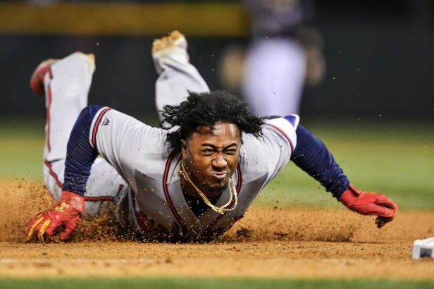Slide 32 of 77: DENVER, CO - APRIL 7: Ozzie Albies #1 of the Atlanta Braves dives back to first base to avoid being doubled off in the ninth inning of a game against the Colorado Rockies at Coors Field on April 7, 2018 in Denver, Colorado.  (Photo by Dustin Bradford/Getty Images)