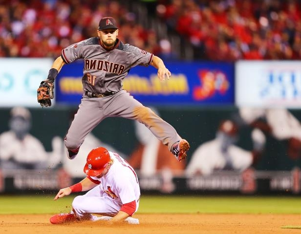 Slide 54 of 77: ST. LOUIS, MO - APRIL 5: Chris Owings #16 of the Arizona Diamondbacks turns a double play over Harrison Bader #48 of the St. Louis Cardinals in the fifth inning at Busch Stadium on April 5, 2018 in St. Louis, Missouri.  (Photo by Dilip Vishwanat/Getty Images)