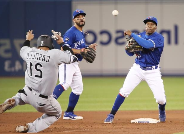 Slide 69 of 77: TORONTO, ON - APRIL 4: Gift Ngoepe #61 of the Toronto Blue Jays turns a double play in the sixth inning over Welington Castillo #21 of the Chicago White Sox at second base at Rogers Centre on April 4, 2018 in Toronto, Canada. (Photo by Tom Szczerbowski/Getty Images)