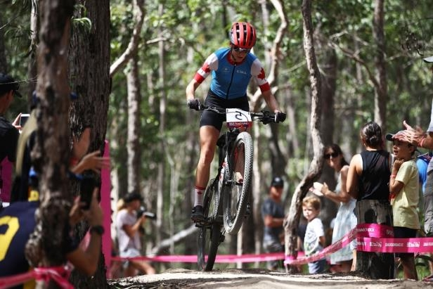 a group of people cross country skiing in the snow: Haley Smith of Canada finished in third in women's cross-country mountain biking at the Commonwealth Games in Gold Coast, Australia on Wednesday.