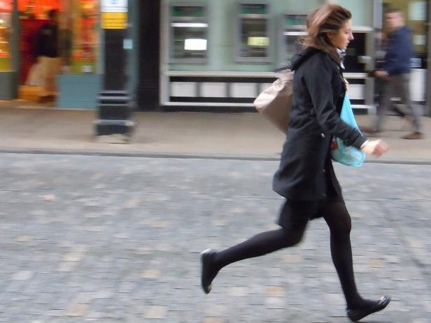 a person walking down a street: running late