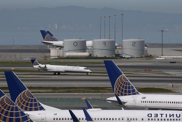 a plane sitting on the tarmac of an airport runway: SAN FRANCISCO, CA - MARCH 13: A United Airlines plane taxis on the runway at San Francisco International Airport on March 13, 2015 in San Francisco, California. According to a passenger survery conducted by SkyTrax, San Francisco International Airport (SFO) was been named the best airport in North America for customer service. SkyTrax collected over 13 million questionnaires at 550 airports around the world. (Photo by Justin Sullivan/Getty Images)