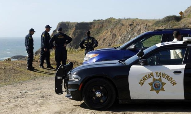 a man standing next to a car: California Highway Patrol officers and deputy sheriffs from Mendocino and Alameda counties gather after a search for three missing children.
