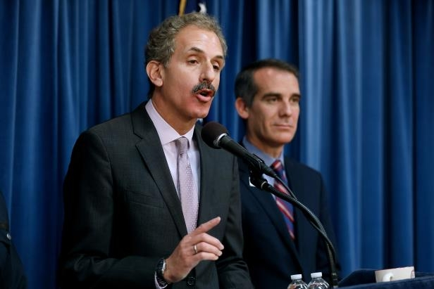 Eric Garcetti in a suit standing in front of a curtain: Los Angeles City Attorney Mike Feuer, right, shown with Los Angeles Mayor Eric Garcetti, details a court ruling against the Trump administration regarding its efforts to withhold federal grants from jurisdictions over their immigration enforcement policies on Thursday, April 12, 2018 at City Hall in Los Angeles, Calif.