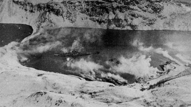 Smoke: The Tirpitz pictured in Kåfjord with the smokescreen seen drifting across the water