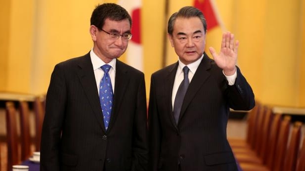 a man wearing a suit and tie: Chinese Foreign Minister Wang Yi Meets With Japanese Counterpart Taro Kono
