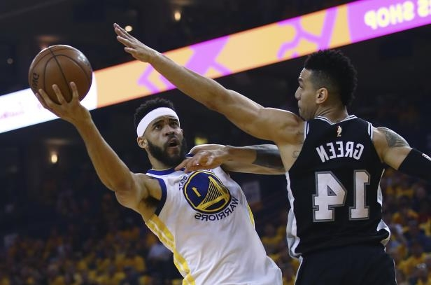 Golden State Warriors' JaVale McGee, right, shoots over San Antonio Spurs' Danny Green (14) during the first half in Game 1 of a first-round NBA basketball playoff series Saturday, April 14, 2018, in Oakland, Calif.