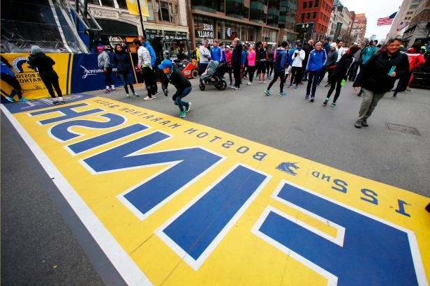 a group of people walking down the street: People gather at the Boston Marathon finish line in Boston on April 15 ahead of Monday's race.