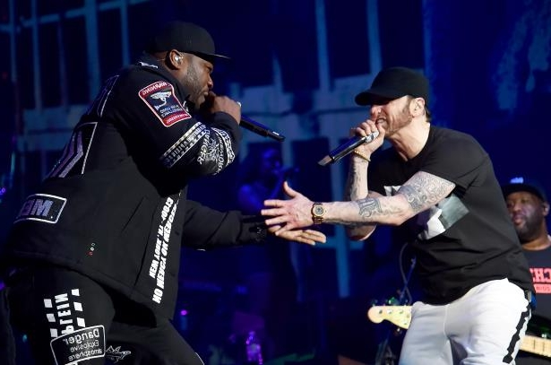 a man standing on a stage: Eminem and 50 Cent