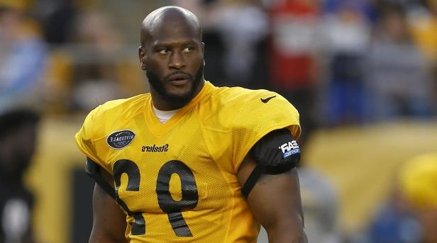 James Harrison wearing a yellow uniform holding a ball