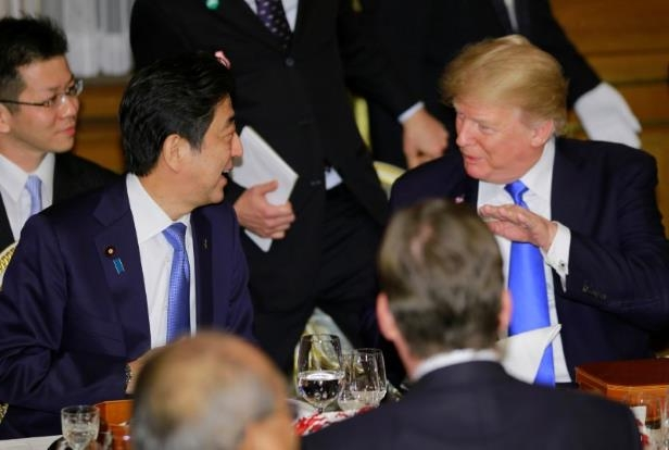 a group of people around each other: U.S. President Donald Trump talks with Japanese Prime Minister Shinzo Abe at the opening of a welcome dinner hosted by Abe at Akasaka Palace in Tokyo