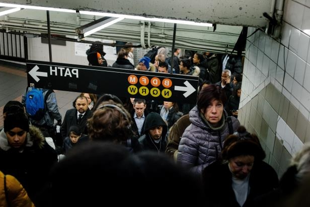 a group of people in a room: A subway station close to a shopping mall gets crowded in New York City on December 20, 2017.