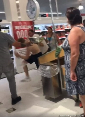 a group of people in a room: Two men have been filmed as they brawled inside of a Coles in Chermside Queensland, as customers watched on with some trying to break it up