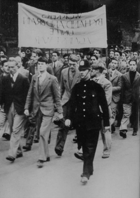 a group of people standing in front of a crowd: Donald Maclean (arrowed in the second rank) taking part in an anti-war march in Cambridge in 1933