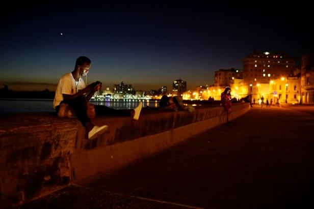 a person with a sunset in the background: Ballet dancer Sandro Calderon, 30, connects to the internet with his mobile at a hotspot in the seafront in Havana