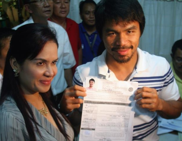 Slide 15 of 22: Philippine boxing hero Manny Pacquiao, left, stands beside wife Jinky as he shows the certificate of candidacy for congress which he filed at the provincial capitol in Sarangani province, southern Philippines on Tuesday Dec. 1, 2009. Pacquiao, considered the world's best pound-for-pound boxer for winning the championship in seven weight classes, will be having his second jab at politics after his 2007 campaign fell short.