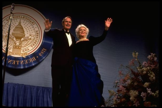 Barbara Bush, George H. W. Bush posing for a picture: Pres. George and Barbara Bush onstage at inaugural ball greeting wellwishers.