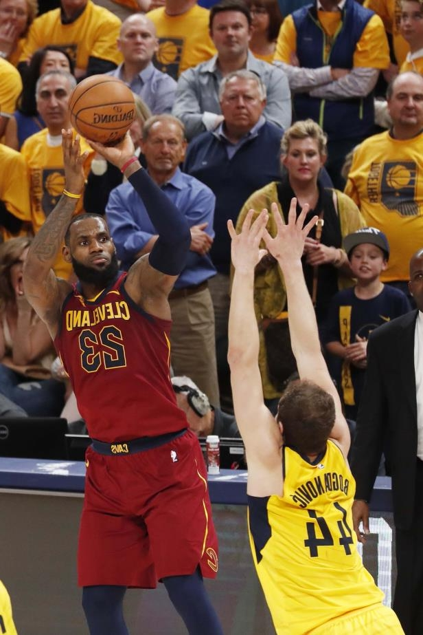 a group of people standing next to a football ball: Cleveland Cavaliers forward LeBron James makes a three-point shot against Indiana Pacers forward Bojan Bogdanovic during the 4th quarter in Game 3.