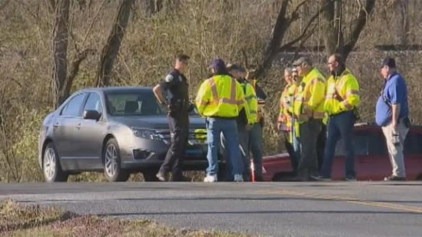 a group of people standing on the side of a road: Authorities discover portion of cache of stolen explosives