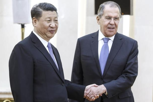 Russia's Foreign Minister Sergei Lavrov (L) and China's President Xi Jinping shake hands ahead of a meeting of foreign ministers of the Shanghai Cooperation Organization (SCO) Member States.