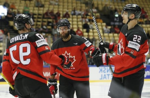 a group of baseball players standing on top of a snow covered field: Canada's Colton Parayko, left, celebrates with teammates Aaron Ekblad, centre, and Connor McDavid, right, after scoring a goal against South Korea at the Jyske Bank Boxen arena in Herning, Denmark, on Sunday.