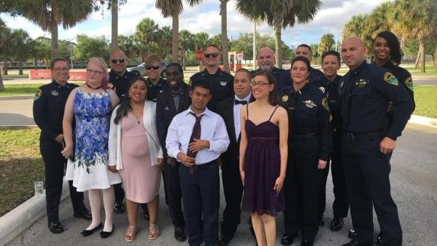 a group of people posing for a photo: Boynton Beach police officers attended prom with several John I. Leonard High students on Saturday.