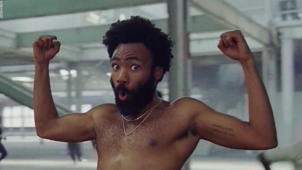 Donald Glover standing in front of a mirror posing for the camera