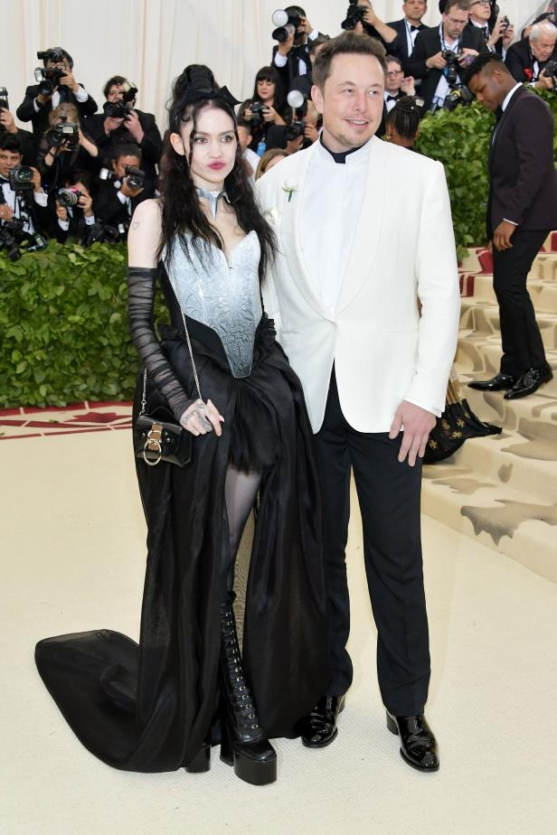 Elon Musk et al. posing for the camera: Elon Musk and Grimes attend The Metropolitan Museum of Art's Costume Institute Benefit celebrating the opening of Heavenly Bodies: Fashion and the Catholic Imagination in New York City on May 7, 2018.