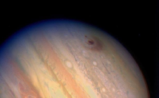 This Hubble telescope image of the giant planet Jupiter reveals the impact sites of two fragments from comet Shoemaker-Levy 9. Twenty-one large chunks of the comet rained down upon Jupiter in July 1994. The impact sites, located in the planet's Southern Hemisphere, are the dark spots in the upper left of the photograph.