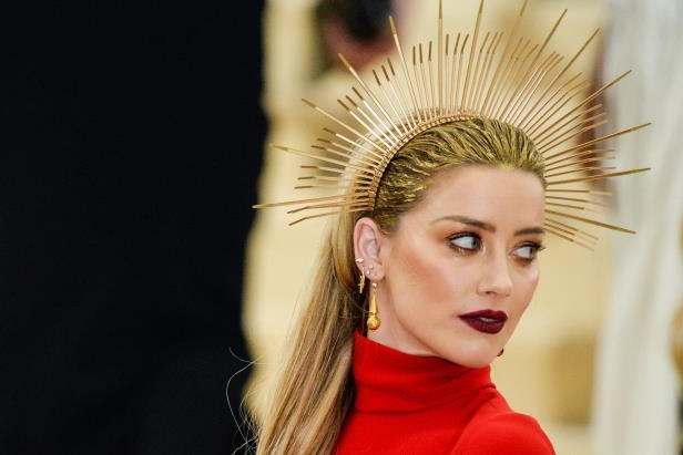 Amber Heard wearing a red hat and looking at the camera