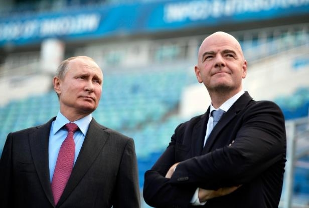 Fatboy Slim wearing a suit and tie: Russian President Vladimir Putin, right, and FIFA president Gianni Infantino visit the Fisht Stadium in the Black Sea resort of Sochi, Russia on May 3, 2018. FIFA has fined Russia after fans racially abused French players during a game in St. Petersburg in March.