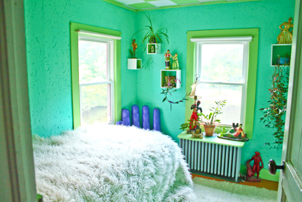 a bedroom with a bed and painted green