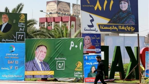 A man walks next to election campaign posters in Baghdad, Iraq: About 7,000 candidates - many of them women - are running in the elections